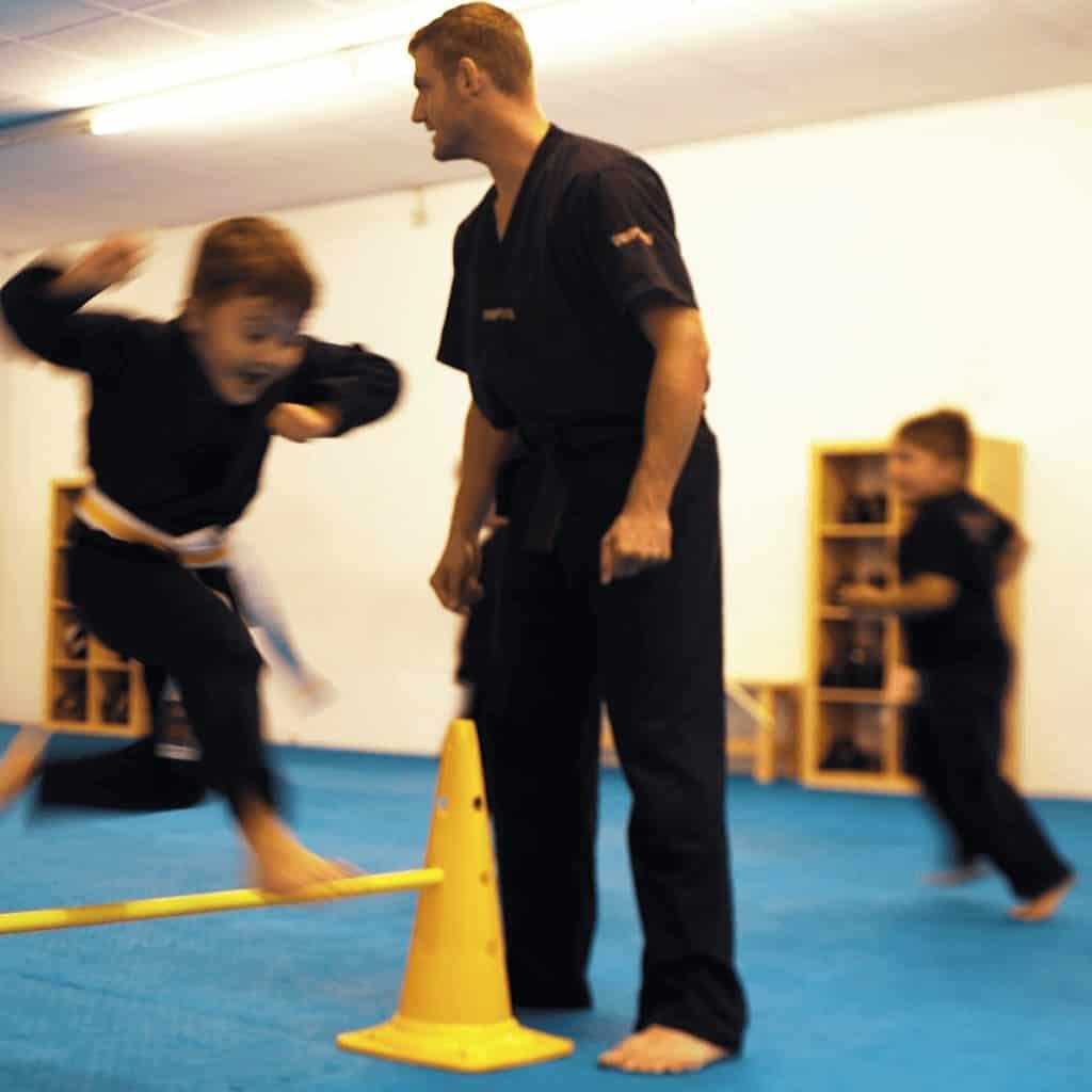 Fröhliches Karate Kind springt über den Parkour