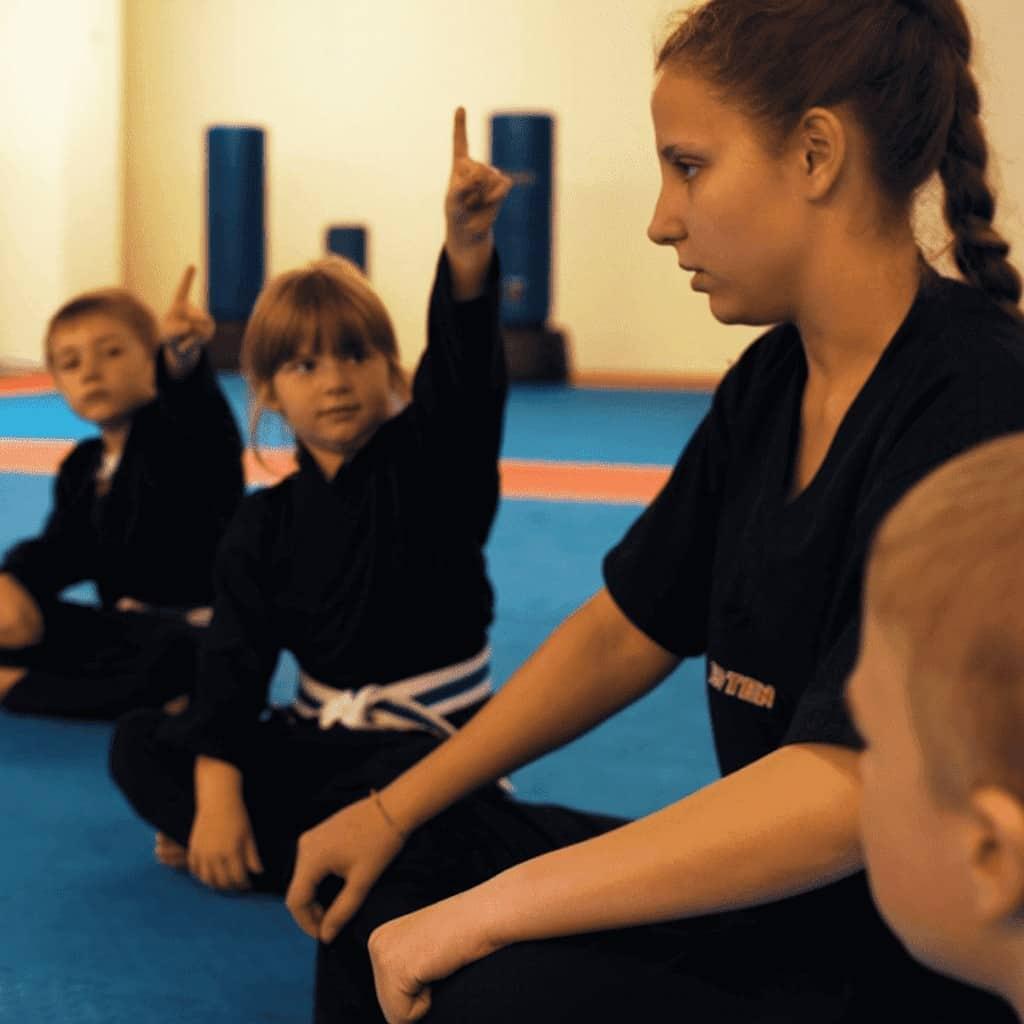 Trainerin mit Kindern im Sitzkreis
