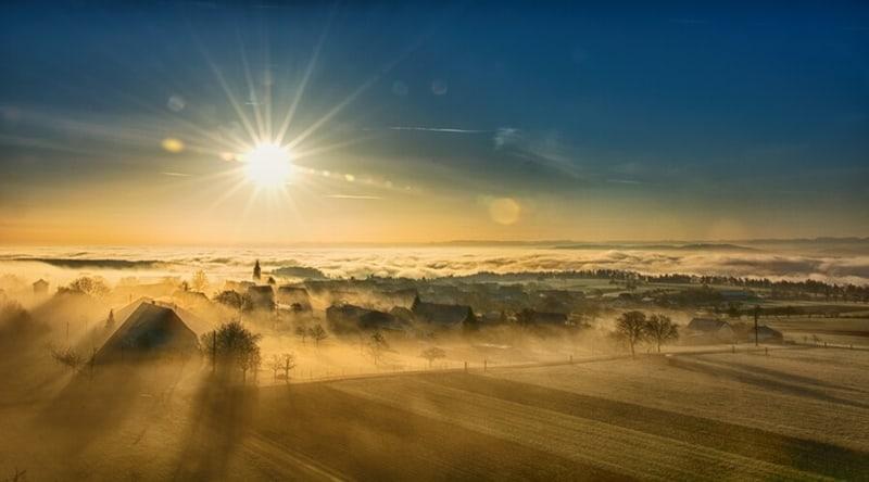 eine Landschaft im Sonnenaufgang mit Morgennebel