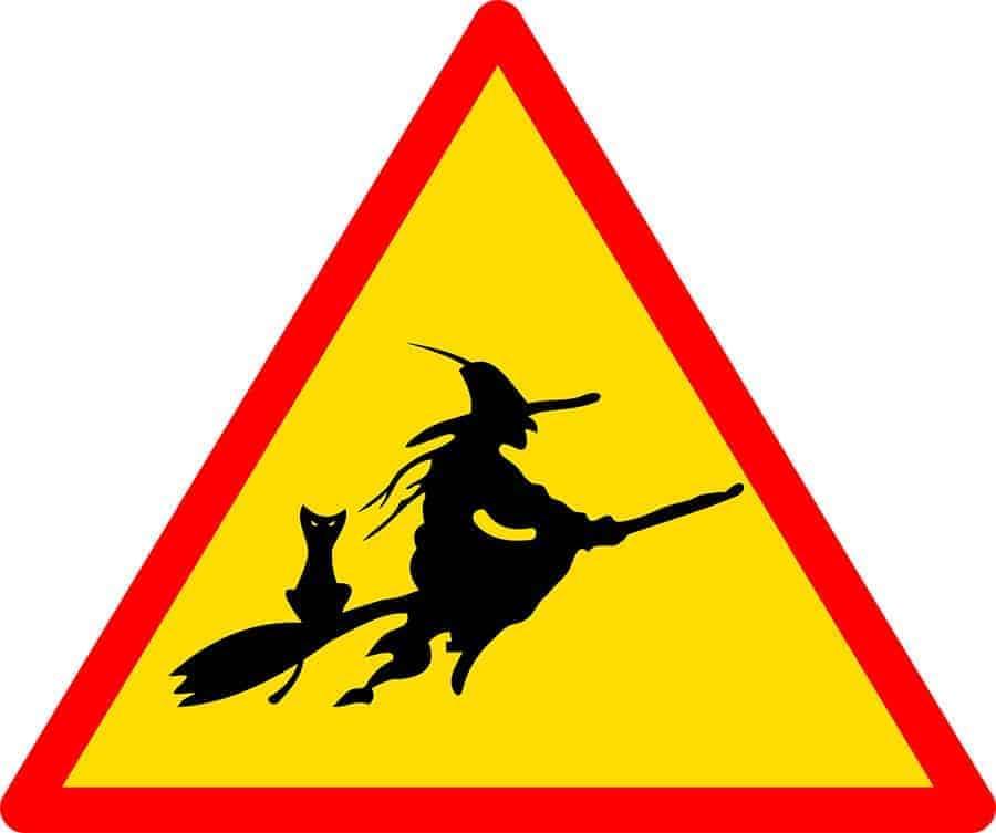 hexe und katze auf einem besen in einem warnschild