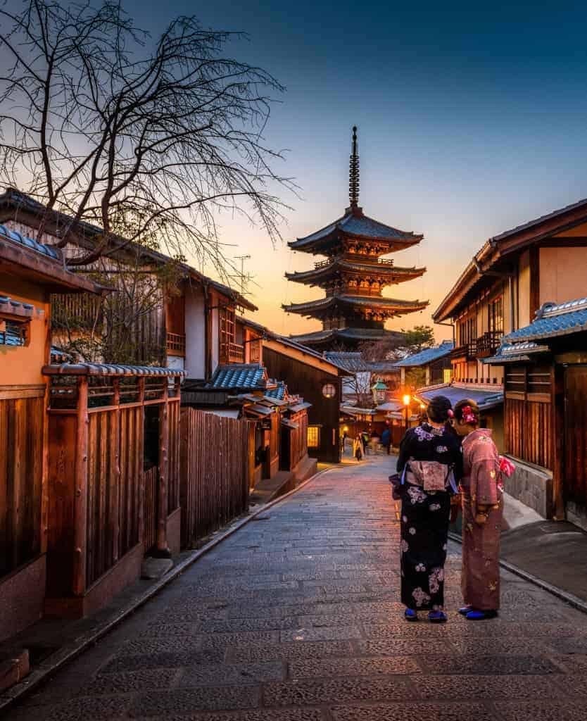 zwei Frauen im Kimono in einem japanischen Dorf mit einem Tempel