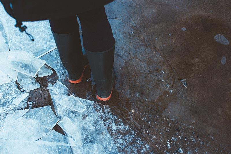 Mit Gummiestiefeln auf einer gefrorenen Pfütze